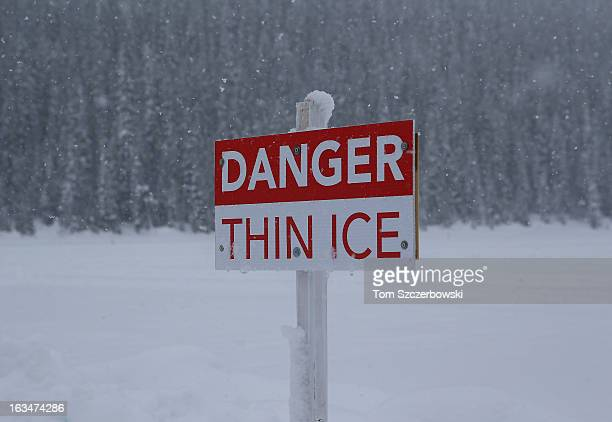 A sign warns of thin ice during an outdoor shinny hockey turnament at the 4th Annual Lake Louise Pond Hockey Classic on the frozen surface of Lake...