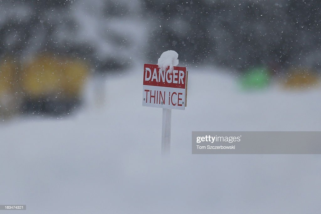 A sign warns of thin ice during outdoor shinny hockey action during the 4th Annual Lake Louise Pond Hockey Classic on the frozen surface of Lake Louise on March 2, 2013 in Lake Louise, Alberta, Canada.