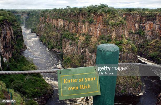 A sign warns tourists from proceeding from a lookout point over the Zambezi River March 17 2008 below Victoria Falls Zimbabwe Called one of the...