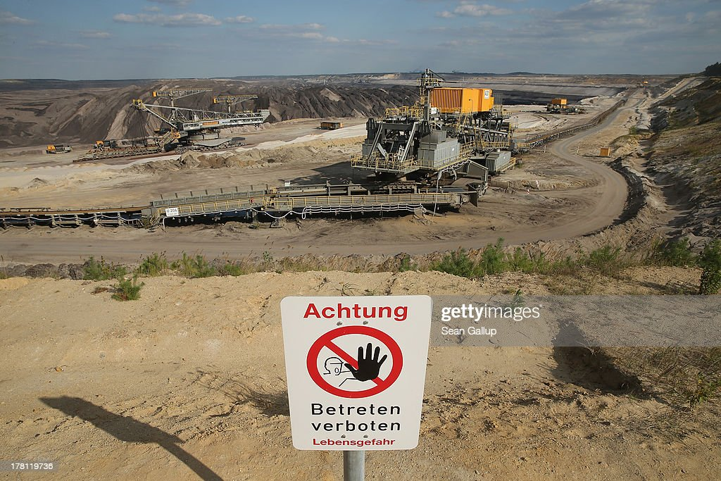 A sign warns visitors not to advance further on the rim of the Welzow Sued open-pit lignite coal mine on August 26, 2013 near Welzow, Germany. Welzow Sued, operated by Vattenfall, is among the last active open-pit mines in a region known as the Lausitzer Seenland, where dozens of former mines have been turned into lakes. In a development project initiated by state government, other nearby former open-pit mines that once evoked a lunar landscape are being turned into lakes in a long-term rejuvenation effort that is also intended to make the area a viable tourist destination. Mineral residue in the mines, however, is proving a difficult stumbling block that is making many of the new lakes too acidic to sustain marine life in the short term.