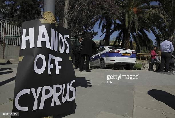 A sign which reads 'Hands off Cyprus' is plastered on an electricity pole outside the pariament building in the Cypriot capital Nicosia on March 18...