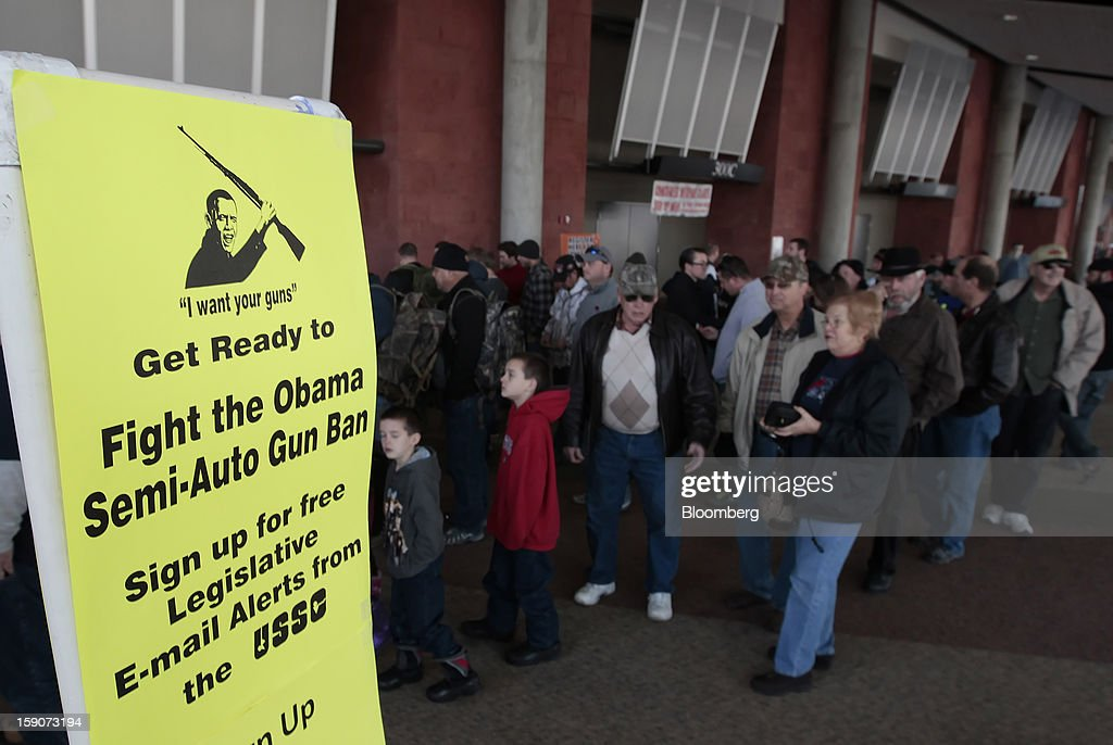 A sign with an image of U.S. President Barack Obama is displayed as people wait to buy tickets for the Rocky Mountain Gun Show in Sandy, Utah, U.S., on Saturday, Jan. 5, 2013. A working group led by Vice President Joe Biden is seriously considering measures that would require universal background checks for firearm buyers, track the movement and sale of weapons through a national database, strengthen mental health checks and stiffen penalties for carrying guns near schools or giving them to minors. Photographer: George Frey/Bloomberg via Getty Images