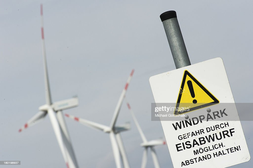 A sign with the inscription Windpark - danger of ice shedding - keep distance, is seen in front of wind turbines near the coast of the north sea on August 29, 2013 in Galmsbuell, Germany. Wind energy rises in german region of Schleswig-Holtstein.