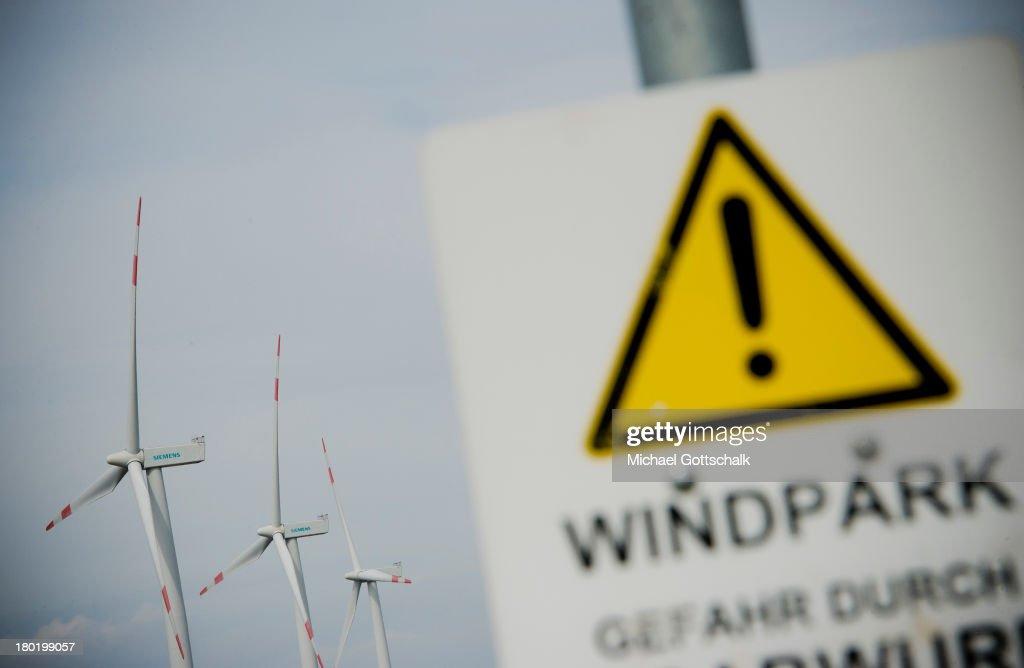 A sign with the inscription Windpark is seen in front of wind turbines near the coast of the north sea on August 29, 2013 in Galmsbuell, Germany. Wind energy rises in german region of Schleswig-Holtstein.