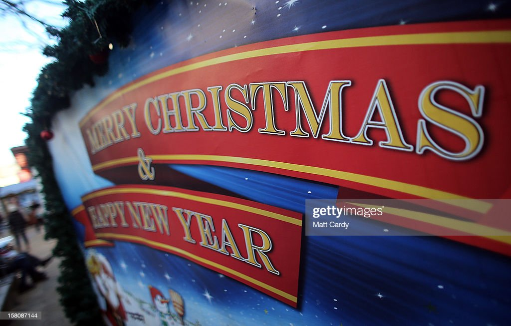 A sign with the message 'Merry Christmas & Happy New Year' is displayed as shoppers browse stalls at a Christmas market on December 10, 2012 in Bristol, England. With internet shopping still on the rise, many traditional retailers claim this Christmas could be the one that will determine the future of the high street.