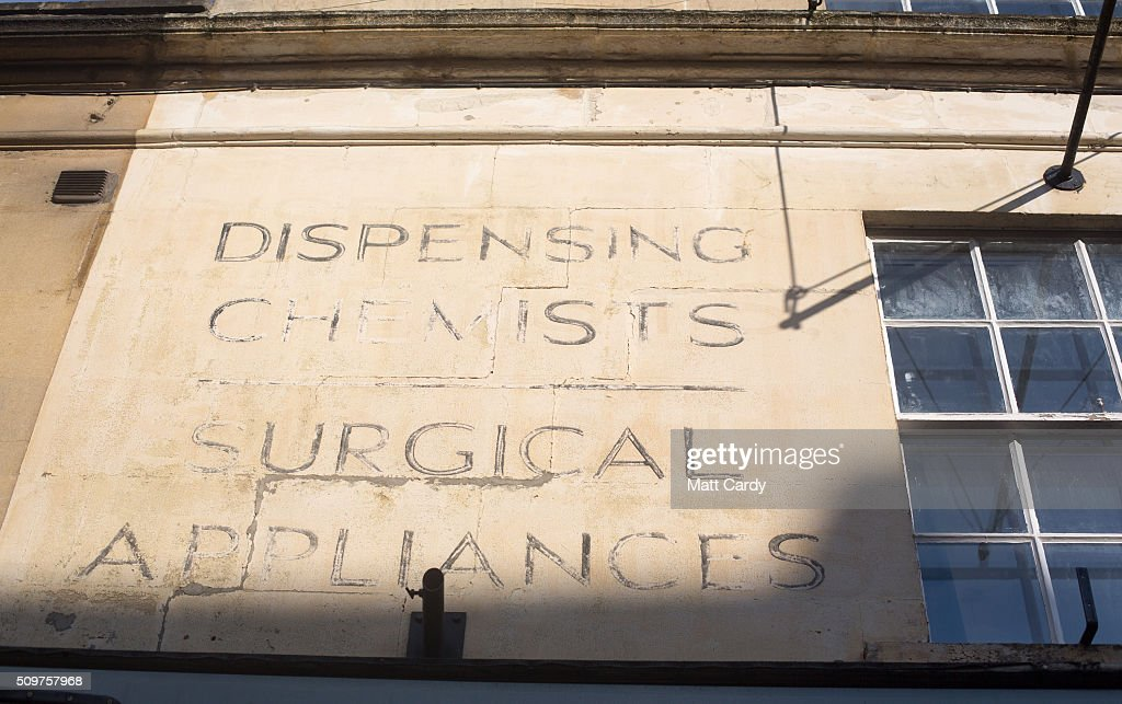 Sign writing refering to an old chemist shop is painted on the exterior of a building now used as an estate agents on February 12, 2016 in Bath, England. One in four high street pharmacies could close as the Government cuts £170 million from the prescription handling fees paid to them.