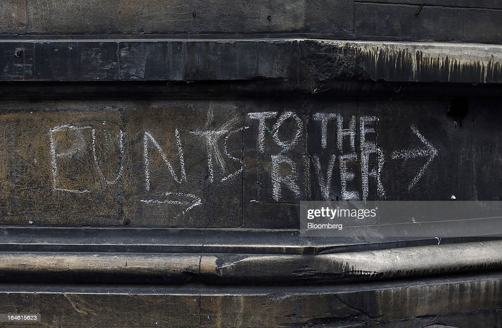 A sign written in chalk on the wall of a dirt-covered building directs tourists to punt trips on the River Cam in Cambridge, U.K., on Friday, March 22, 2013. In 2011, the U.K.'s government unveiled a plan to reduce state spending on higher education and shift more of the costs to students through tuition increases and a loan program. Photographer: Chris Ratcliffe/Bloomberg via Getty Images