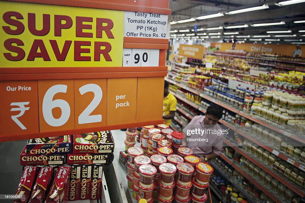 Signage displays 'super saver' deals above customers browsing packaged foods at the Big Bazaar Hypermarket store in Noida, India, on Monday, Sept. 9, 2013. Indias rupee fell, snapping the biggest four-day surge in 40 years, on concern slowing growth will deter inflows needed to reduce the current-account deficit. Photographer: Prashanth Vishwanathan/Bloomberg via Getty Images