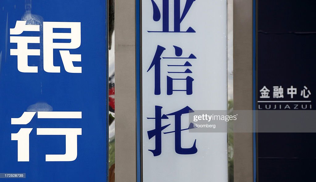 Signage featuring the Chinese characters for 'bank', left, and 'trust', center, are displayed next to a sign for the Lujiazui financial center in Shanghai, China, on Monday, July 1, 2013. Chinese banks' valuations are close to their lowest on record as the nation's interbank funding crisis exacerbated investors' concern that earnings growth will stall and defaults may surge as the economy slows. Photographer: Tomohiro Ohsumi/Bloomberg via Getty Images