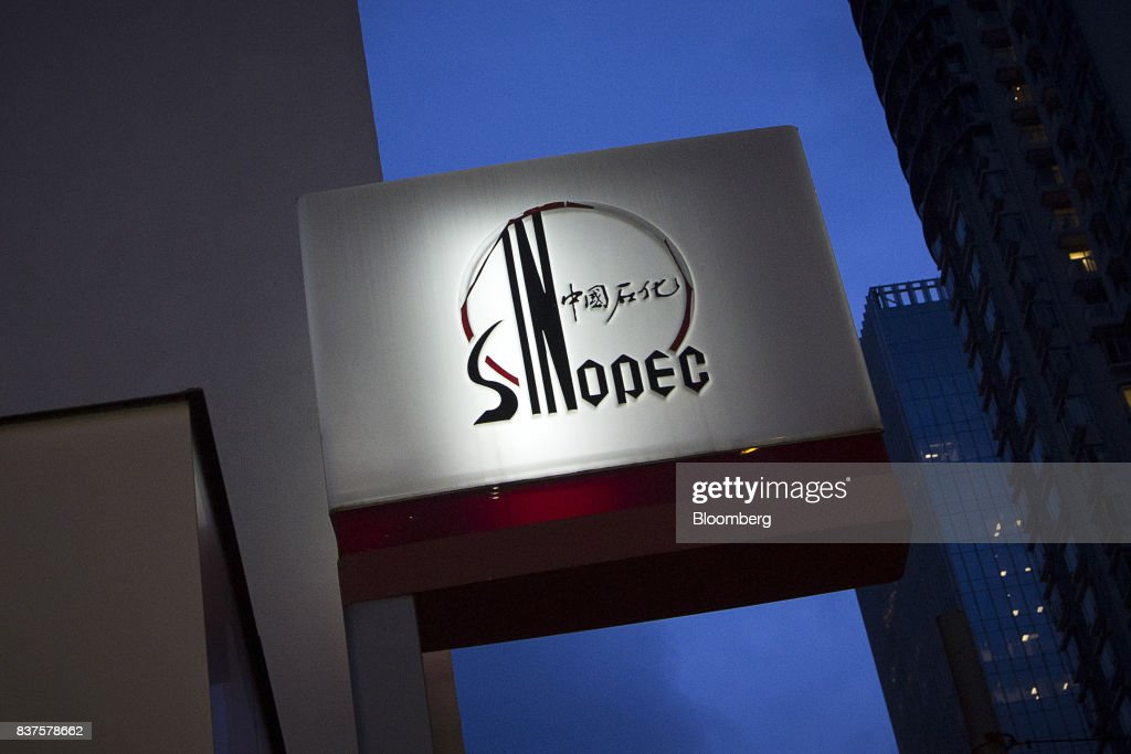 Signage for a China Petroleum & Chemical Corp. (Sinopec) gas station stands illuminated at dusk in Hong Kong, China, on Tuesday, Aug. 22, 2017. Sinopec is scheduled to report second-quarter results on Aug. 25. Photographer: Vivek Prakash/Bloomberg via Getty Images