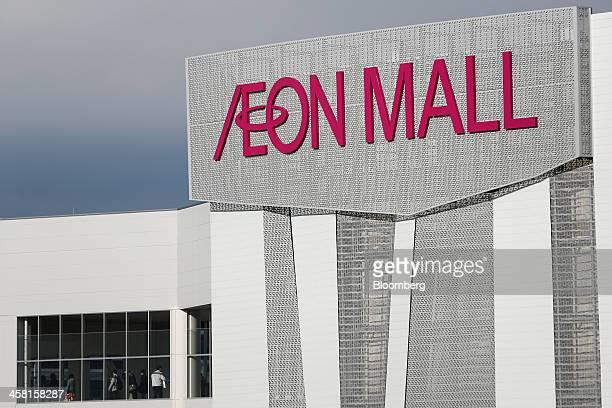 Signage for Aeon Co is displayed as customers walk through the Aeon Mall Makuhari Shintoshin shopping mall operated by Aeon Mall Co in Chiba Japan on...