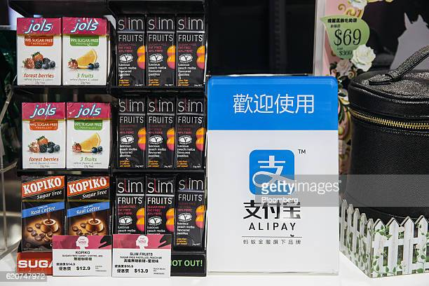 Signage for Ant Financial Services Group's Alipay an affiliate of Alibaba Group Holding Ltd is displayed next to candies for sale inside a Sa Sa...