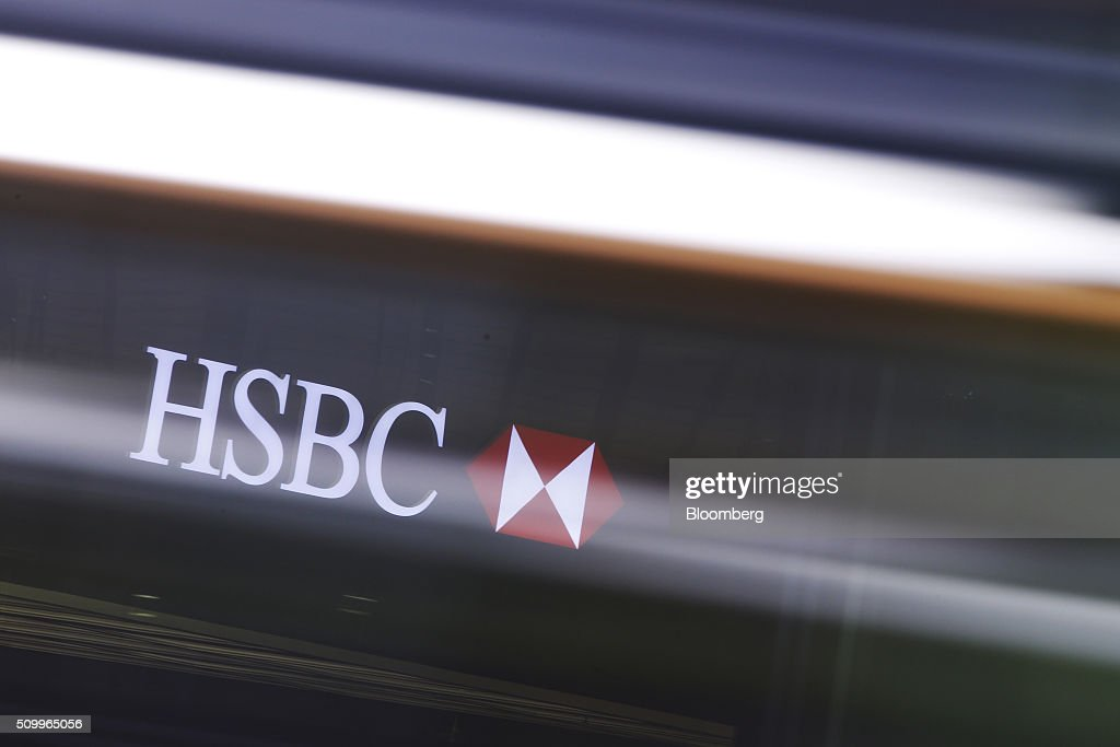 Signage for HSBC Holdings Plc, seen through a passing bus, sits on the company headquarters in the Canary Wharf business, financial and shopping district in London, U.K., on Saturday, Feb. 13, 2016. HSBC's board will meet on Sunday to decide whether to shift its headquarters from London, according to two people with knowledge of the decision. Photographer: Luke MacGregor/Bloomberg via Getty Images