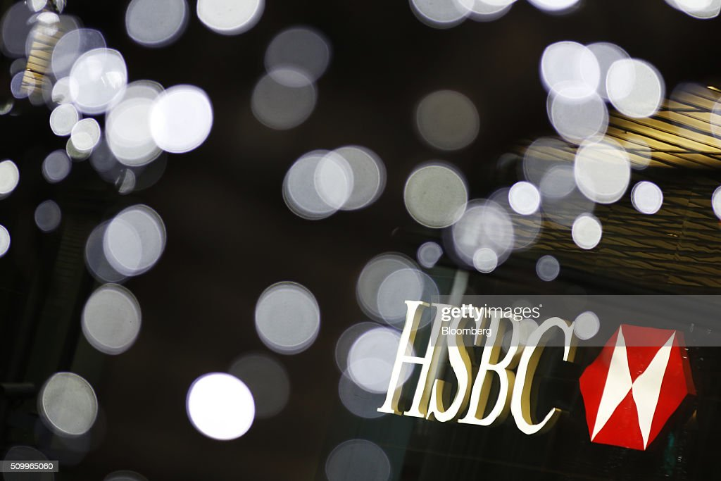 Signage for HSBC Holdings Plc, sits illuminated amongst decorative lights at the company headquarters in the Canary Wharf business, financial and shopping district in London, U.K., on Saturday, Feb. 13, 2016. HSBC's board will meet on Sunday to decide whether to shift its headquarters from London, according to two people with knowledge of the decision. Photographer: Luke MacGregor/Bloomberg via Getty Images