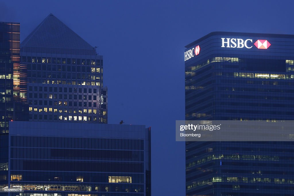 Signage for HSBC Holdings Plc, sits illuminated atop the company headquarters in the Canary Wharf business, financial and shopping district, at dawn in London, U.K., on Saturday, Feb. 13, 2016. HSBC's board will meet on Sunday to decide whether to shift its headquarters from London, according to two people with knowledge of the decision. Photographer: Luke MacGregor/Bloomberg via Getty Images