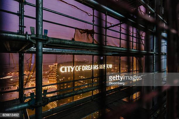 Signage for Melco Crown Entertainment Ltd's City of Dreams casino resort is seen through scaffolding from Morpheus the company's new hotel tower...