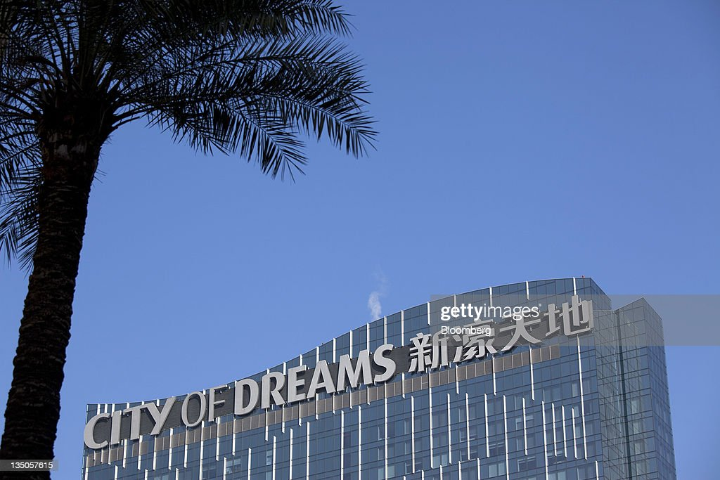 Signage for Melco Crown Entertainment Ltd.'s City Of Dreams is displayed on top of one of the Grand Hyatt Hotel towers in Macau, China, on Sunday, Dec. 4, 2011. Macau casino gambling revenue climbed a better-than-expected 33 percent last month as economic growth stoked demand from visitors from China's mainland. Photographer: Jerome Favre/Bloomberg via Getty Images