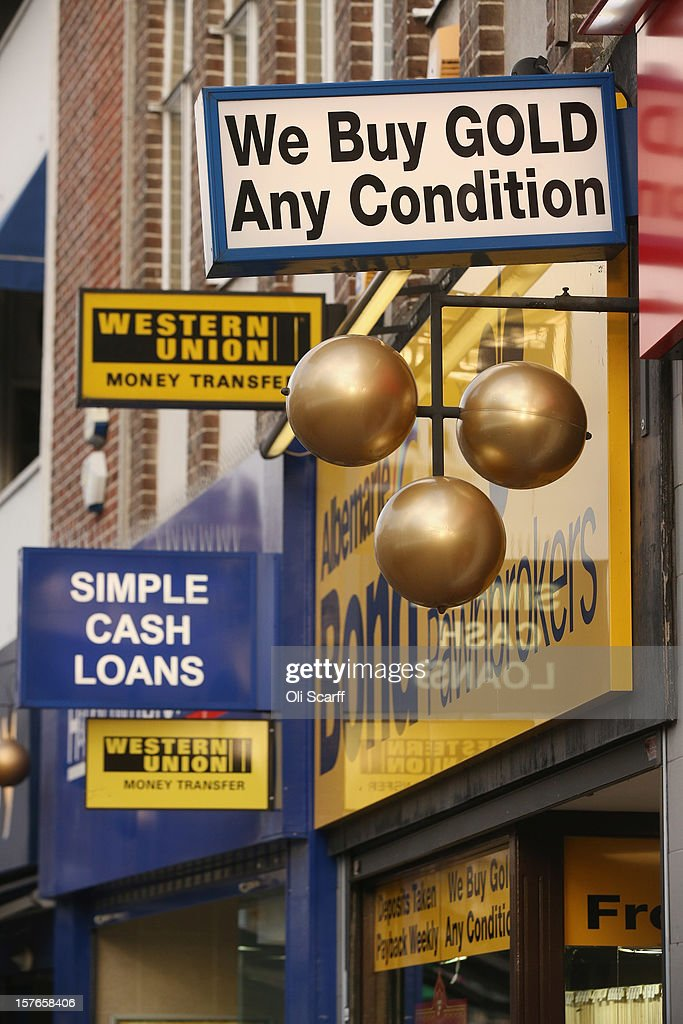 Signage for pawnbroker shops on Lewisham high street on December 5, 2012 in London, England. The Chancellor of the Exchequer George Osborne has stated that the United Kingdom's economy is still struggling during his autumn budget statement to Parliament.
