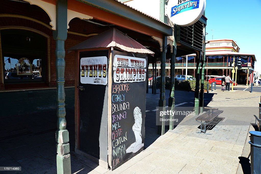 Signage for 'Skimpies', female staff who work in their underwear or burlesque outfits, stands outside the bar of the Exchange Hotel in Kalgoorlie, Australia, on Wednesday, Aug. 7, 2013. Kalgoorlie, a town in the Goldfields-Esperance region of Western Australia, is home to the annual Diggers & Dealers mining forum. Photographer: Carla Gottgens/Bloomberg via Getty Images
