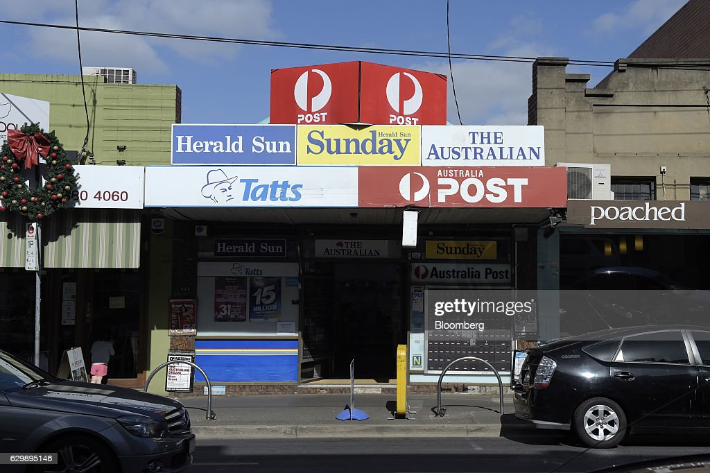 Signage for Tatts Group Ltd. and Australian Postal Corp. is displayed above a newsagent's store in Melbourne, Australia, on Thursday, Dec. 15, 2016. A consortium including Morgan Stanley and KKR & Co. offered as much as A$7.3 billion ($5.5 billion) for Australian betting and lotteries business Tatts Group, setting up a potential bidding war with Tabcorp Holdings Ltd. Photographer: Carla Gottgens/Bloomberg via Getty Images