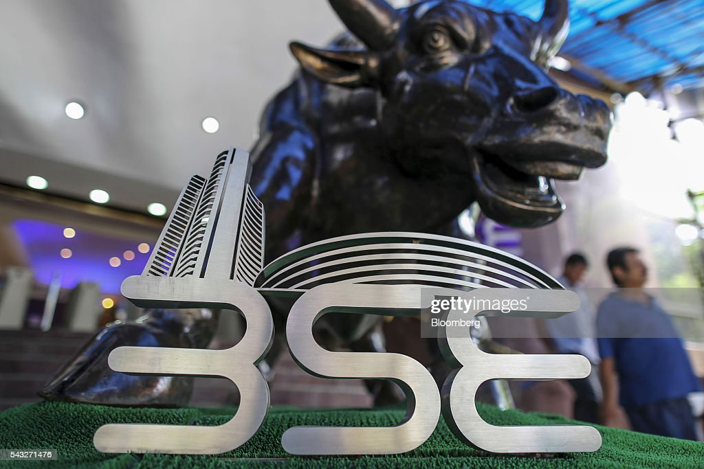Signage for the Bombay Stock Exchange (BSE) is displayed next to a bronze bull statue at the entrance to the BSE building in Mumbai, India, on Monday, June 27, 2016. Most Indian stocks advanced, led by companies tied to the economy, as some investors judged Friday's Brexit-induced selloff is overdone. Tata Consultancy Service Ltd. (TCS) and Infosys Ltd., India's top software exporters that earn about a quarter of their revenue from Europe, were the biggest losers on the benchmark S&P BSE Sensex. Photographer: Dhiraj Singh/Bloomberg via Getty Images