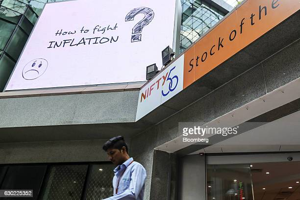 Signage for the CNX Nifty Index is displayed as an employee walks through the atrium of the National Stock Exchange of India Ltd building in Mumbai...