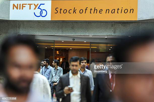 Signage for the CNX Nifty Index is displayed as employees walk through the atrium of the National Stock Exchange of India Ltd building in Mumbai...