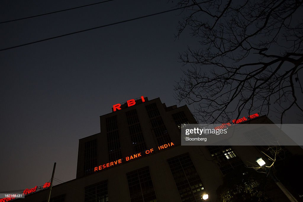 Signage for the Reserve Bank of India (RBI) is illuminated at night in the BBD Bagh area of Kolkata, India, on Tuesday, Feb. 19, 2013. India's slowest economic expansion in a decade is limiting profit growth at the biggest companies even as foreigners remain net buyers of the nation's stocks, according to Kotak Institutional Equities. Photographer: Brent Lewin/Bloomberg via Getty Images