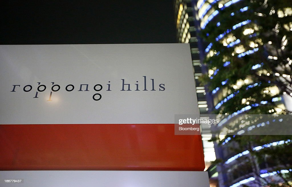 Signage for the Roppongi Hills Mori Tower, operated by Mori Building Co., stands at night in Tokyo, Japan, on Tuesday, April 17, 2013. While financial firms have cut staff in Japan, technology companies have boosted hiring, and as bankers vacated offices at Roppongi Hills, companies including Google Inc. and Lenovo Group Ltd. moved in. As early as this month, Apple Inc. will also make the complex its home in Japan, two people familiar with the plan said in January. Photographer: Tomohiro Ohsumi/Bloomberg via Getty Images