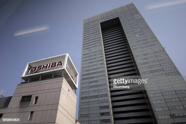 Signage for Toshiba Corp displayed atop the company's headquarters is seen through a monorail train window in Tokyo Japan on Tuesday March 28 2017...