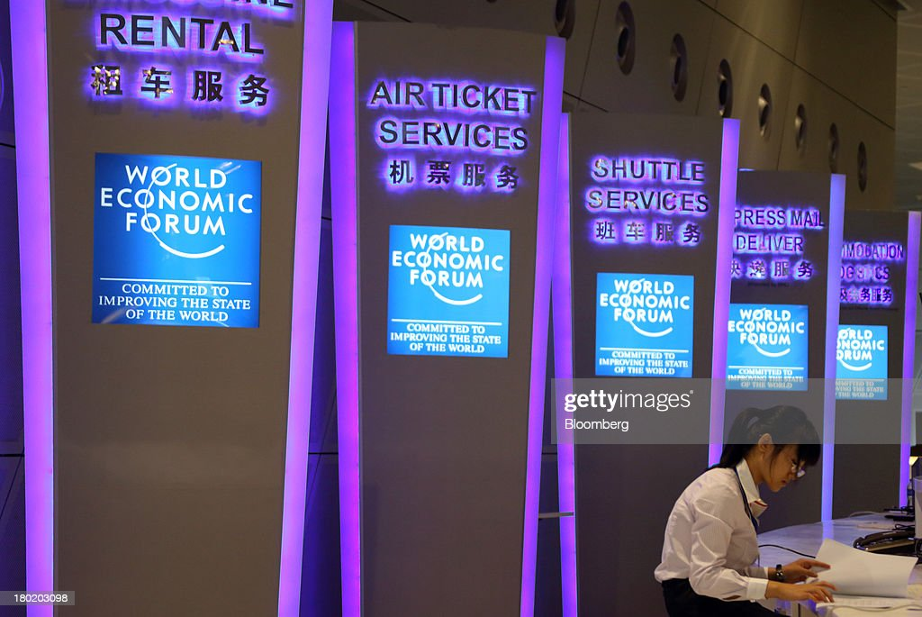 Signage for various services is displayed along with the World Economic Forum logo as a staff member works on a desk at the Dalian International Conference Center in Dalian, China, on Tuesday, Sept. 10, 2013. The World Economic Forum Annual Meeting Of The New Champions 2013 will be held in Dalian from Sept. 11 to 13. Photographer: Tomohiro Ohsumi/Bloomberg via Getty Images
