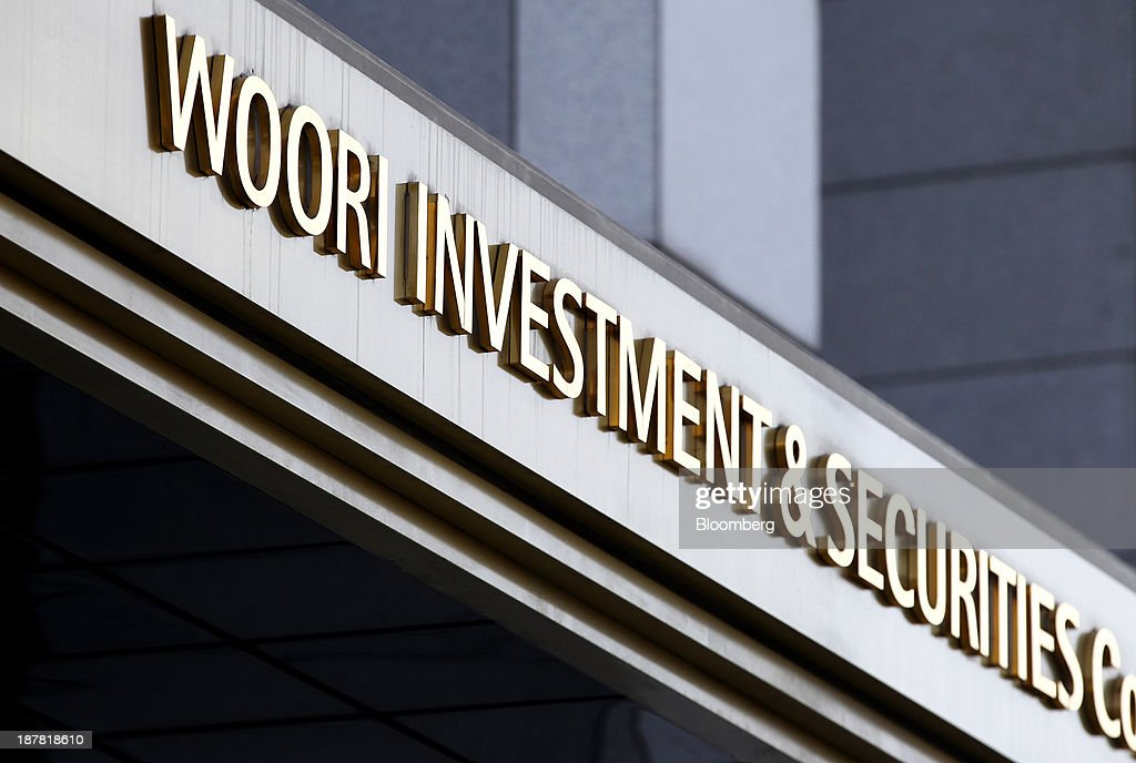 Signage for Woori Investment & Securities Co., a unit of Woori Finance Holdings Co., is displayed outside the company's headquarters in Seoul, South Korea, on Tuesday, Nov. 12, 2013. Woori Finance Holdings is scheduled to report third-quarter results on Nov. 14. Photographer: SeongJoon Cho/Bloomberg via Getty Images