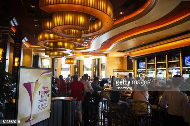 signage is displayed as customers dine in the bar area of a Cheesecake Factory Inc restaurant in the Canoga Park neighborhood of Los Angeles...