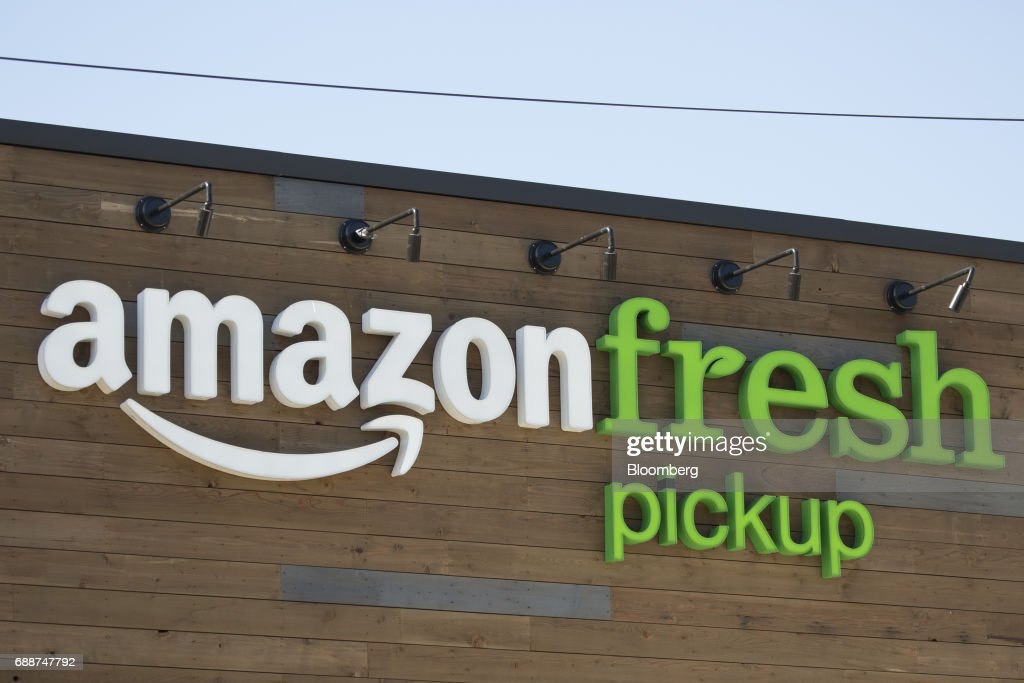 Signage is displayed at an AmazonFresh Pickup location in Seattle, Washington, U.S., on Friday, May 26, 2017. Amazon.com Inc. opened two grocery pickup kiosks in Seattle, part of its latest effort to enter the $800 billion grocery market and compete with 'click and collect' shopping options from big box competitors like Wal-Mart Stores Inc.