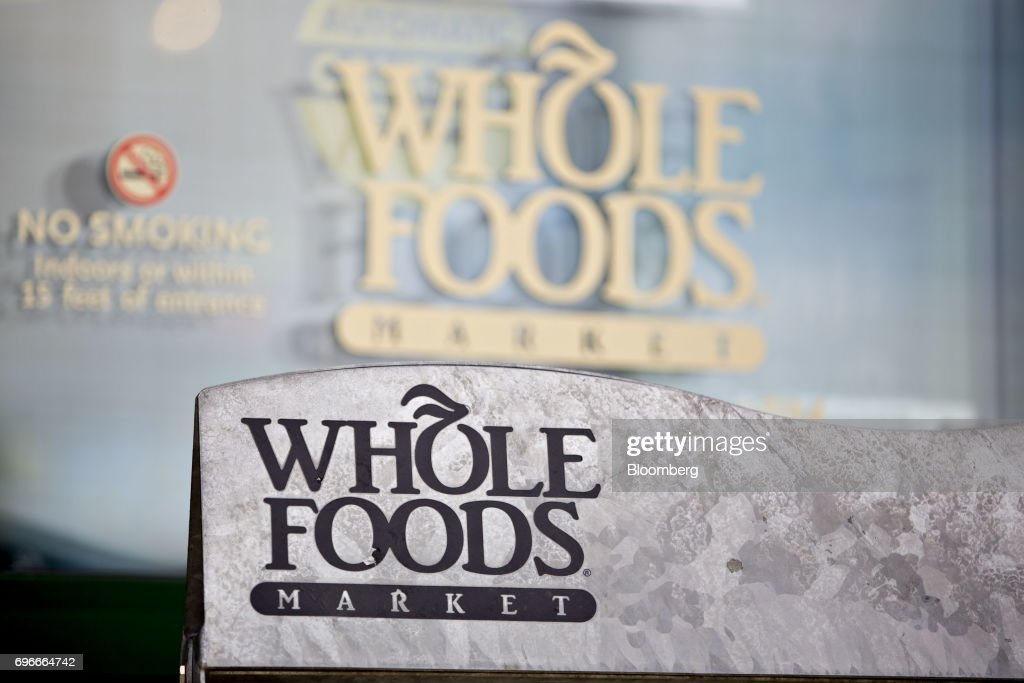 Signage is displayed outside a Whole Foods Market Inc. location in Naperville, Illinois, U.S., on Friday, June 16, 2017. Amazon.com Inc. will acquire Whole Foods Market Inc. for $13.7 billion, a bombshell of a deal that catapults the e-commerce giant into hundreds of physical stores and fulfills a long-held goal of selling more groceries. Photographer: Daniel Acker/Bloomberg via Getty Images