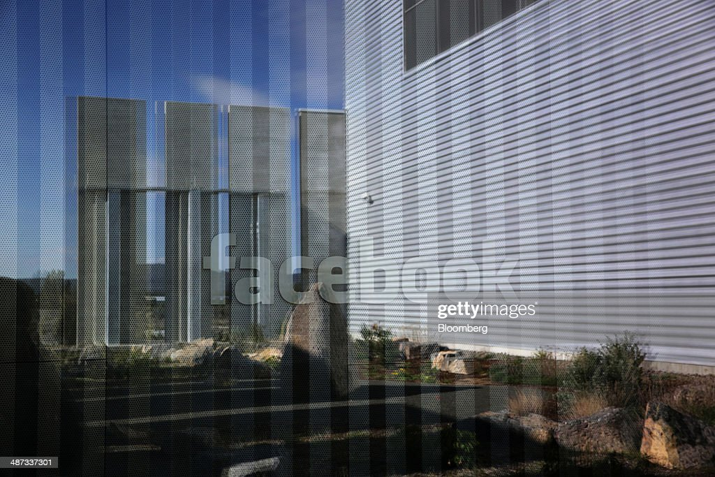 Signage is reflected in a window at the Facebook Inc. Prineville Data Center in Prineville, Oregon, U.S., on Monday, April 28, 2014. The Facebook Prineville Data Center features leading energy-efficient technology, including features such as rainwater reclamation, a solar energy installation for providing electricity to the office areas and reuse of heat created by the servers to heat office space. Photographer: Meg Roussos/Bloomberg via Getty Images
