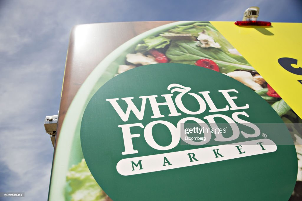 Signage is seen on a catering vehicle outside a Whole Foods Market Inc. location in Willowbrook, Illinois, U.S., on Friday, June 16, 2017. Amazon.com Inc. will acquire Whole Foods Market Inc. for $13.7 billion, a bombshell of a deal that catapults the e-commerce giant into hundreds of physical stores and fulfills a long-held goal of selling more groceries. Photographer: Daniel Acker/Bloomberg via Getty Images