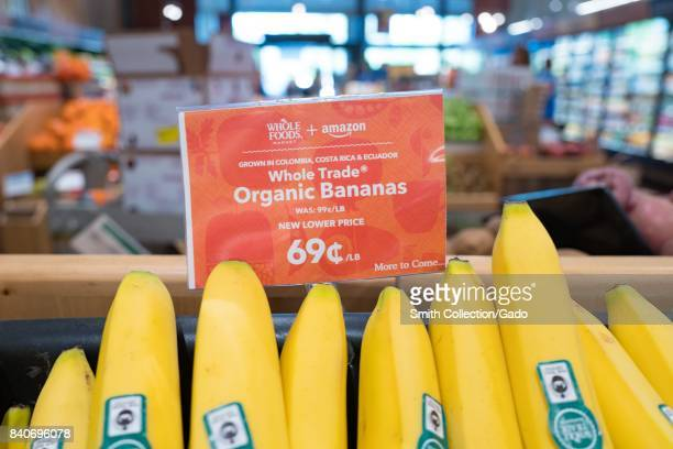 Signage on a display of bananas at the Whole Foods Market store in San Ramon California reading 'Whole Foods Market and Amazon New Lower Price More...