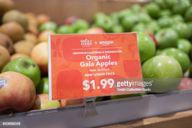 Signage on a display of Gala apples at the Whole Foods Market store in San Ramon California reading 'Whole Foods Market and Amazon New Lower Price...