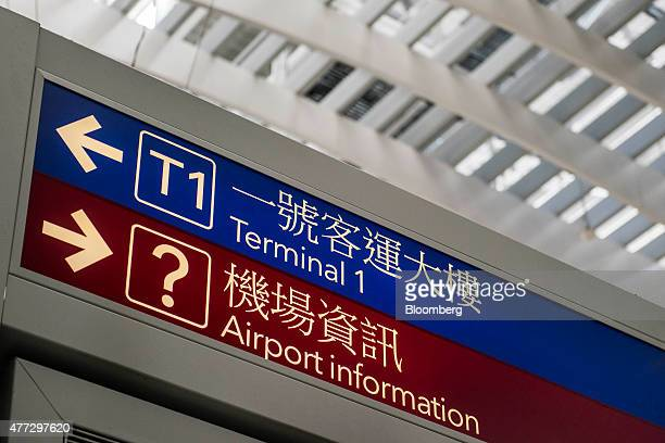 Signage points to Terminal 1 and the airport information desk at Terminal 2 of Hong Kong International Airport in Hong Kong China on Monday June 15...