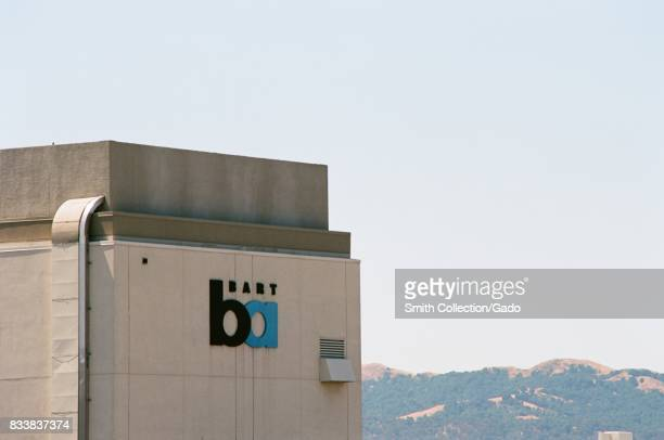 Signage with logo for the Bay Area Rapid Transit light rail system at the Pleasant Hill California station with Diablo foothills visible in the...