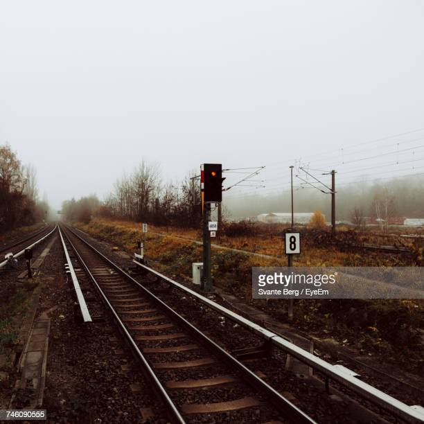 Signal By Railroad Tracks Against Sky During Foggy Weather