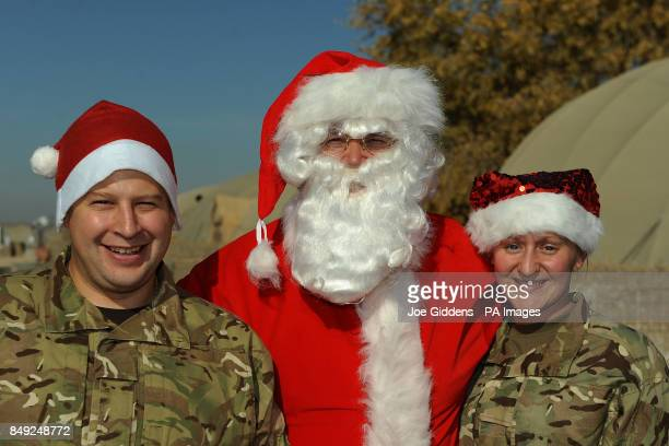 Signalman Carl Ridehalgh from Lancashire and Corporal Michelle Smith from Derby pose for a photo with Santa on Christmas Day in main operating base...