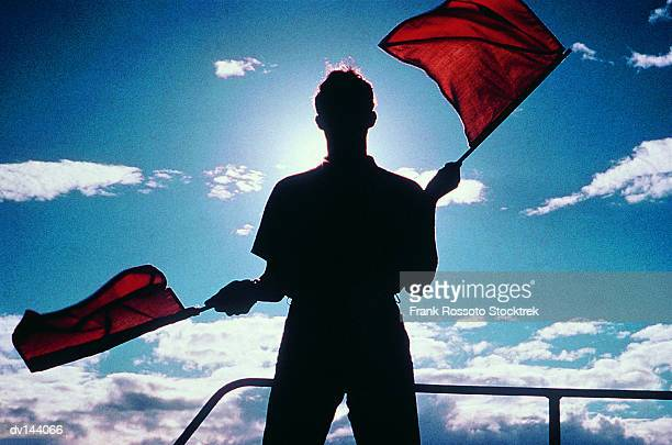 Signalman waving flags, silhouetted against sun