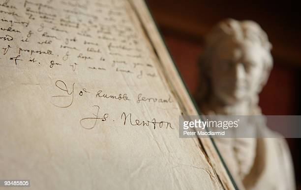 A signature of Isaac Newton contained in a book of his letters is displayed next to a statue of him at the Royal Society on November 24 2009 in...