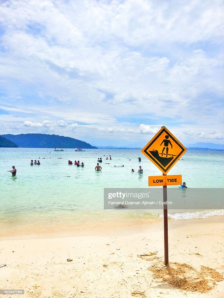 Signboard on shore with in sea at beach