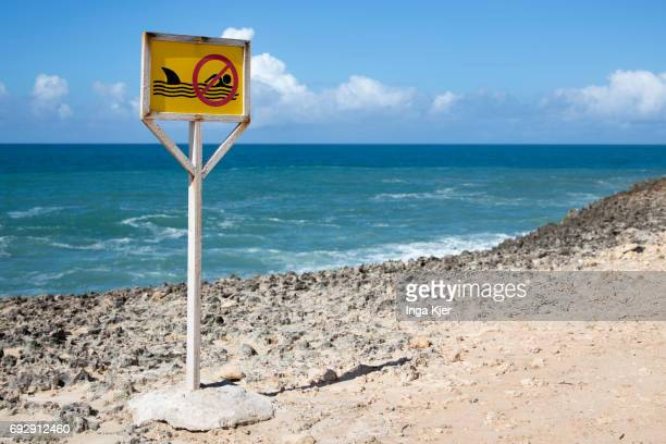 A signboard which prohibits swimming due to the danger of sharks stands on a beach on May 01 2017 in Mogadischu Somalia