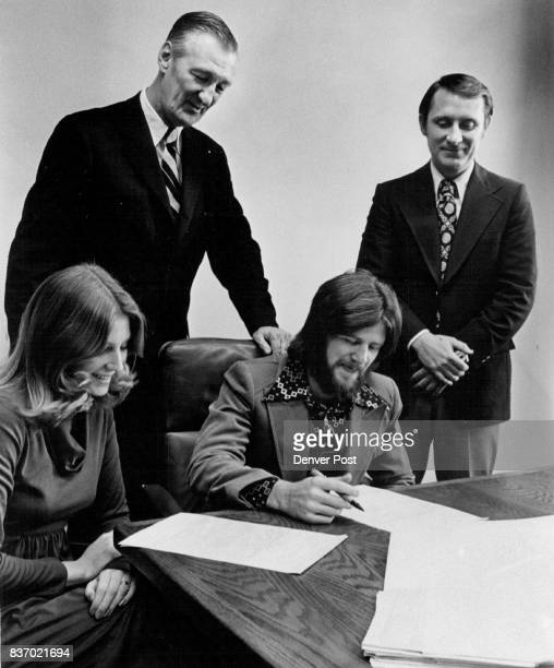 Signing For New Mortgage Payment Plan New home owners Robert Buck and wife seated standing from left Robert Derrington the First Denver Mortgage Co...