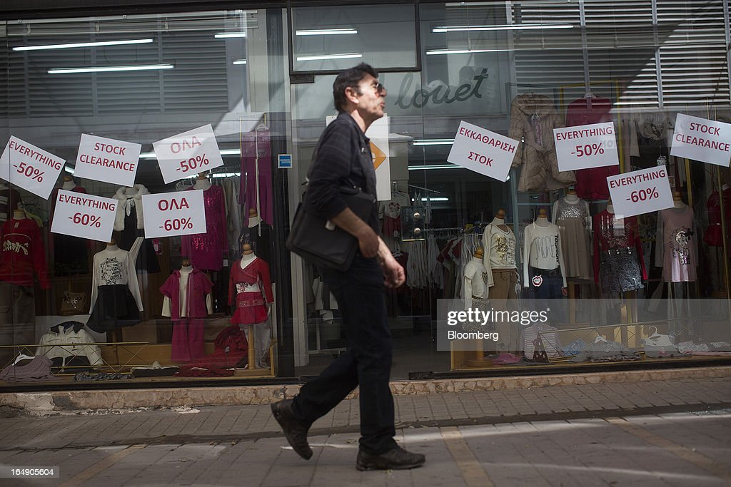 Signs advertise a stock clearance sale and reductions of up to 60% in the window display of a clothing store in Nicosia, Cyprus, on Friday, March 29, 2013. Cypriots face a second day of bank controls over their use of the euro as officials in Europe urged the country to move quickly to lift the restrictions, the first time they have been imposed on the common currency. Photographer: Simon Dawson/Bloomberg via Getty Images