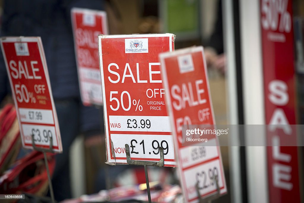 Signs advertising sales discounts of 50 per cent are seen on goods outside a souvenir store on Oxford Street in central London, U.K., on Monday, Feb. 25, 2013. U.K. Chancellor of the Exchequer George Osborne won't bow to opposition calls to change economic plans after the decision by Moody's Investors Service to strip the U.K. of its Aaa status. Photographer: Jason Alden/Bloomberg via Getty Images